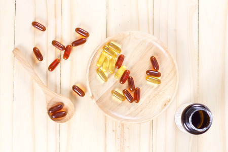 aphrodisiac: Closeup the yellow soft gelatin supplement fish oil capsule on wooden plate. Stock Photo
