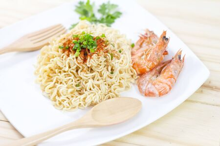 instant noodles: Instant noodles food in white on wooden background. Stock Photo