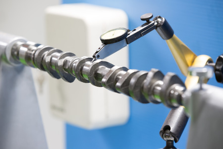 turning operation: cam shaft inspection runout by centering and dial gauge Stock Photo