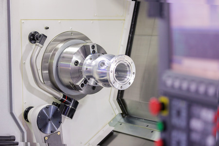 affixment: operator turning aluminium autopart by cnc lathe in industrial factory Stock Photo