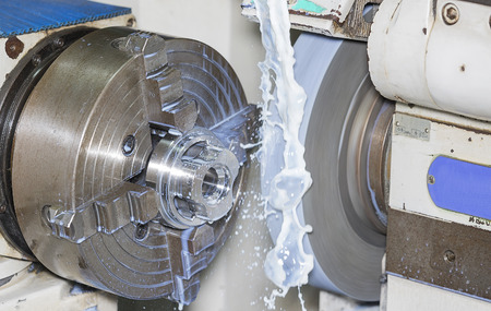 turn dial: operator grinding mold and die part by universal grining machine in factory_01 Stock Photo