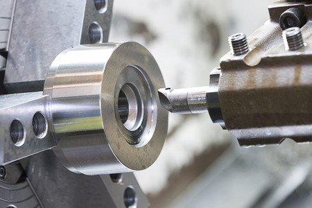 operator machining mold and die part by CNC turning machine in factory