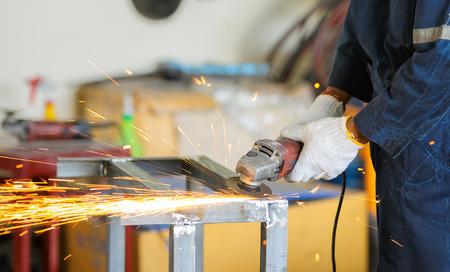 tool and die: worker grinding steel by grinding machine