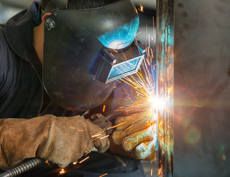 skilled labour: worker welding construction by MIG welding Stock Photo