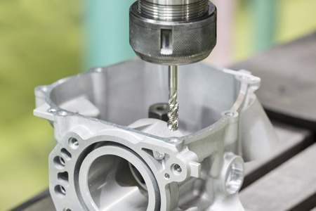 tooling: Tapping aluminum automotive part by cnc machining center Stock Photo