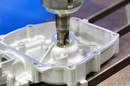 metal processing: operator milling aluminum automotive part by cabide milling
