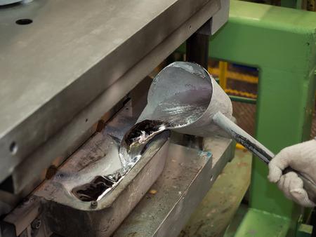 注湯取鍋でアルミ部品を注いで演算子 写真素材