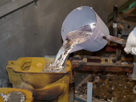 metal: operator pouring aluminum automotive parts by pouring ladle