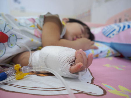 little girl on a drip receiving a saline solution in hospital