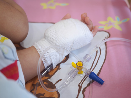 saline solution: little girl on a drip receiving a saline solution in hospital