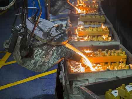 Operator gieten moltem metaal in schimmel op casting productielijn Stockfoto - 42063284
