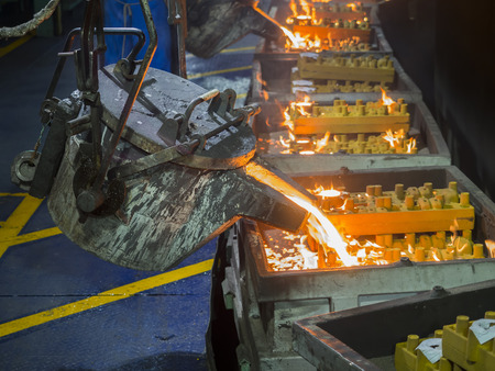 metal casting: operator pouring moltem metal in mold on casting production line