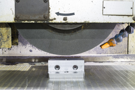 machine tool: operator grinding surface of mold and die parts by surface grinding machine