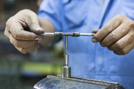 operator tapping mold parts by hand and carbide