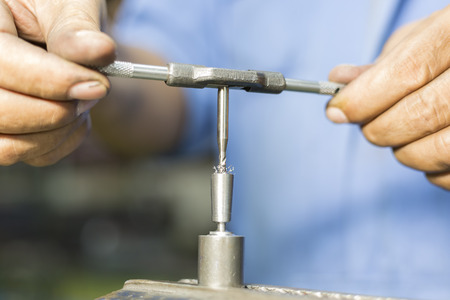 tapping: operator tapping mold parts by hand and carbide