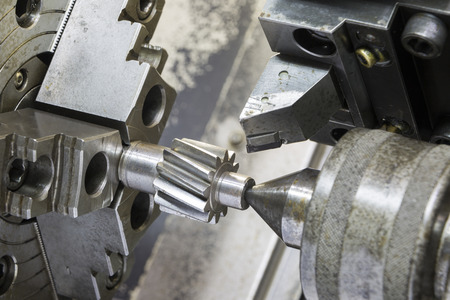 tool chuck: Operator machining automotive gear by cnc turning machine Stock Photo