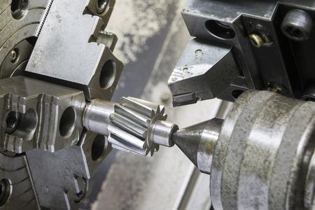 close up: Operator machining automotive gear by cnc turning machine Stock Photo
