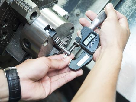 Exploitant inspectie dimensie van machinig delen micrometer Stockfoto