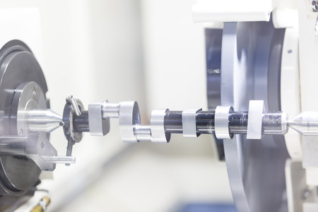 tool and die: operator grinding mold and die part by universal grining machine