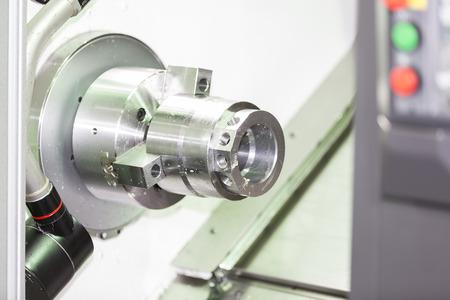 tool chuck: Operator machining automotive part by cnc turning machine Stock Photo