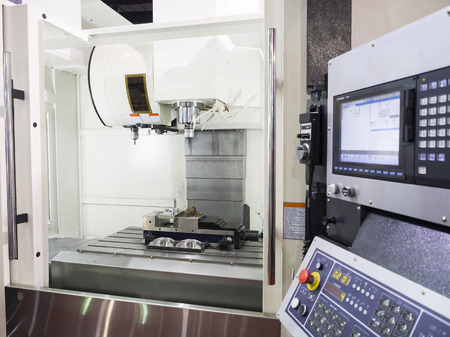 automated tooling: machining precision part by CNC machining center Stock Photo