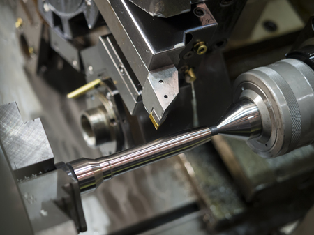 tool chuck: operator machining mold and die part by CNC turning machine in factory