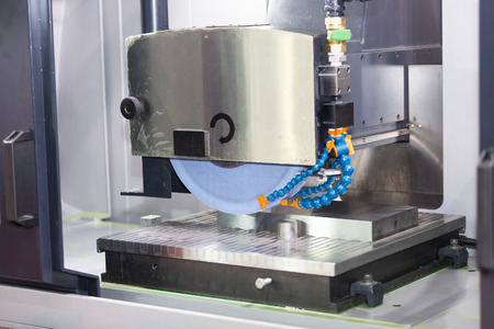 operator grinding surface of mold and die parts by surface grinding machine