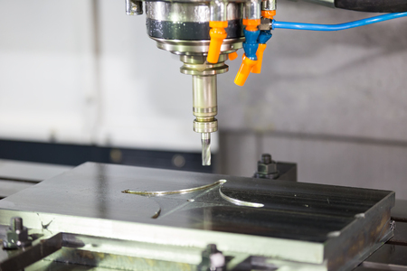tool and die: machining precision part by CNC machining center Stock Photo