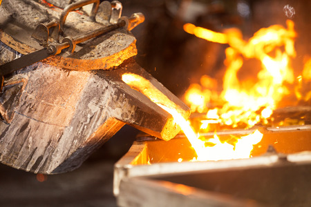Opérateur versant le métal en fusion dans la ligne de coulée automatique dans l'usine de fonderie, la fusion électrique, la fabrication de pièces de coulée de haute précision