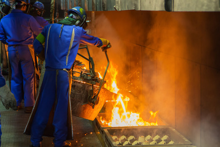 crucible: Operator pouring molten metal in automatic casting line in foundry factory, electric melting, high precision casting part manufacturing Stock Photo