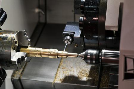 cnc旋回機による自動車部品の加工を行うオペレータ