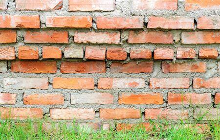 Brick wall orange color and a grass photo