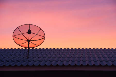 Silhouetted satellite dish on the roof in sunset sky Stock Photo - 17602770