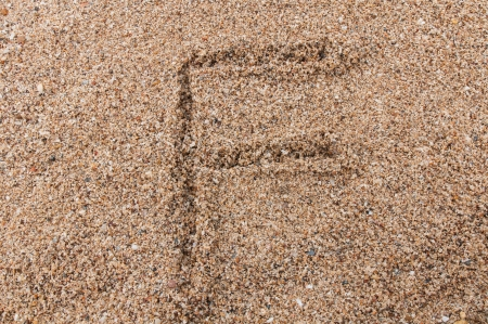 Character F of the alphabet writing on the sand photo
