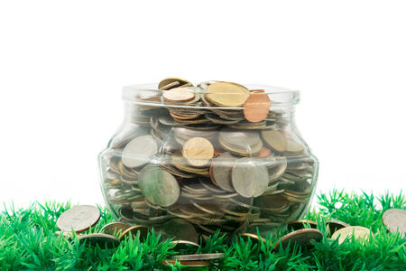 glass jar full of bath coins on artificial grass on white background photo