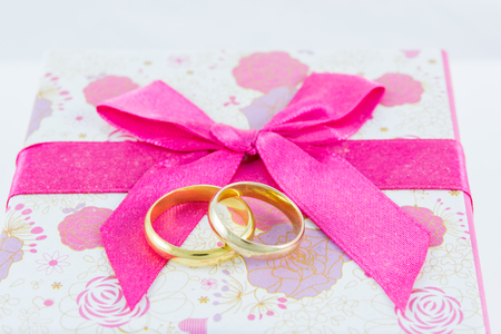 Wedding rings on gift box on white background photo