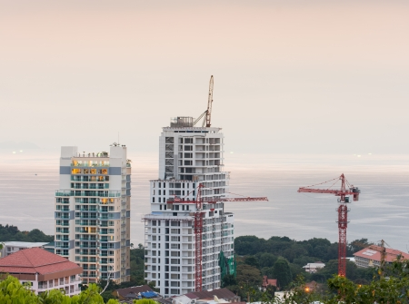 buildings under construction and cranes and the sea photo