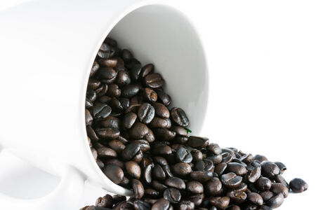 Spilled coffee beans on white ceramic cup isolated background photo