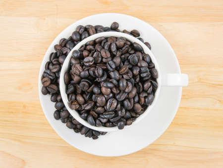 top coffee beans in white cup on brown background photo