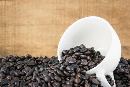 coffee beans in white cup on brown background photo