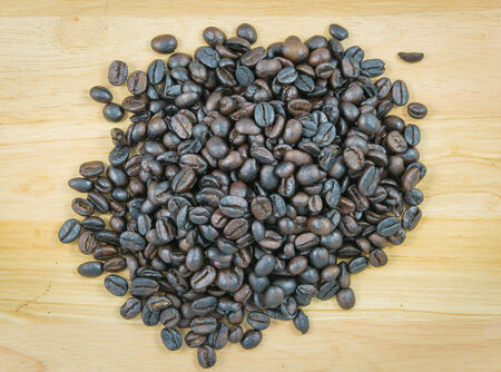 coffeetree: Coffee beans on wood on brown background Stock Photo
