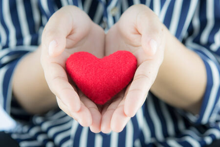 Giving love with hands holding a red heart photo
