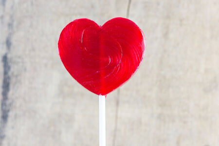 Heart shaped colorful lollipop on wooden background photo