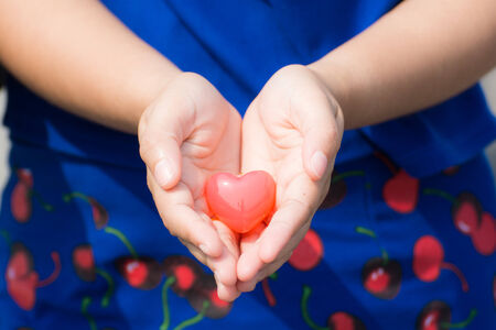 Red heart holding on hands and blue background photo