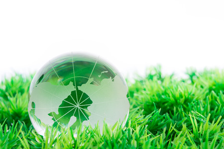 glass globe in the grass on white background photo
