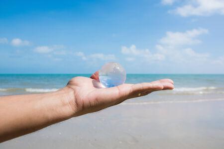 hand holding glass globe with beautiful beach view  photo