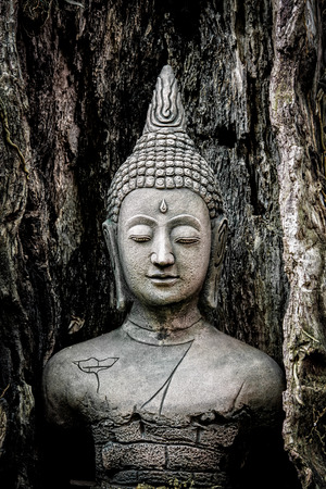 buddha face: Old buddha statue on a wooden background Stock Photo