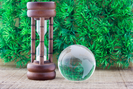 Wood hourglass countdown start and the globe on green grass background photo