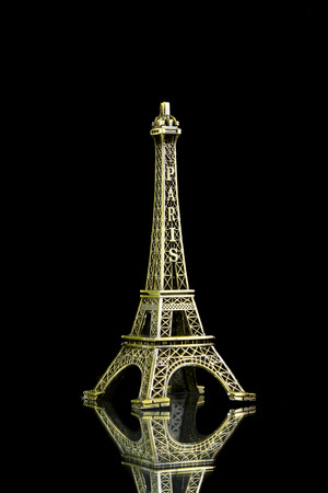 Small Eiffel tower isolated on over black background photo