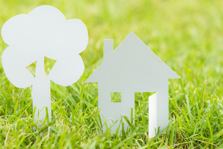 House white paper cut concept in green field background photo